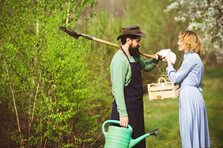 Wife and husband planting in the vegetable garden. Gardening in spring - happy couple harvesting and having lots of fun. Banco de Imagens