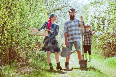 Happy family on farm. Family gardening in the backyard garden. Happy family having fun at countryside. Banco de Imagens