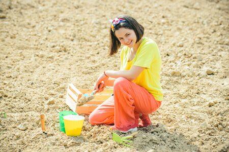 Happy girl having fun with shovel and plant in pot. Planting seedlings. Little helper in garden Planting flowers. Child farmer concept.