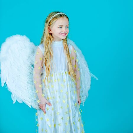 Little angel Girl in white dress with angel wings on isolated background. Christmas Cute little Angel. Pretty little angel girl. Child with angelic face.