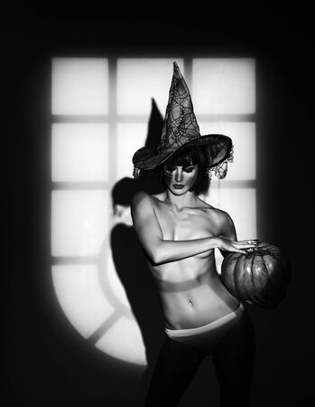 Sexy stripper Woman with pumpkins. Night time halloween party for adult. Sunsual desire concept. Halloween lingerie model. Zdjęcie Seryjne
