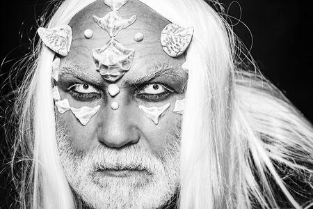Elderly man holding two red horns. Burning diabolic demon summons evil forces and opens hell. Evil vampire man. Devil horror concept. Bearded old man dressed like Halloween monster. Imagens