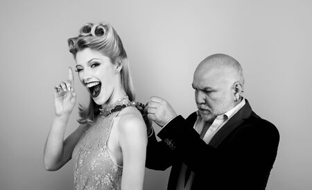 Rich elder man with grey hair. Blonde woman eye wink at camera. Happy blonde woman with luxury hairstyle and makeup smile while her sugar daddy wears a decoration on her neck.