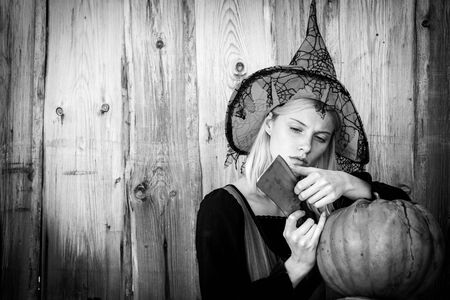Girl preparing to cut a pumpkin. Witch in halloween hat posing outdoor. Portrait of young women in halloween costumes over outdoor wood background.