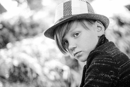 Cute little child boy on farm village background. Boy looking at camera. Close-up portrait. Childhood in the farm. Good time in the village. Childrens fashion hat for autumn.