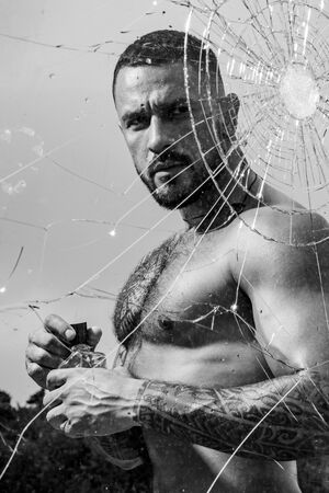 mental problem. bullet hole in glass. broken glass because of hit. sexy hispanic man broken mirror. anger. destruction. macho man behind crushed glass. crush test. theft. emotional discharge