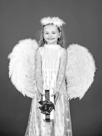 Angel child from heaven gives you gift. Cute toddler girl in white wings as Cupid. Angel kid with blonde curly hair. Happy little Angel. Wonderful blonde little girl in the image of an angel with white wings.