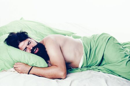 Young man sleeping on soft pillows in bed at home. Napping man concept. Man sleeping on pillow in bed at home.