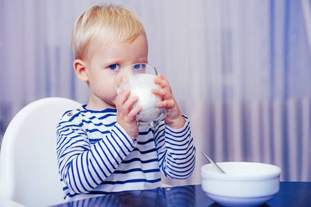 Baby nutrition. Eat healthy. Toddler having snack. Healthy nutrition. Drink milk. Child hold glass of milk. Kid cute boy sit at table with plate and food. Healthy food. Boy cute baby eating breakfast