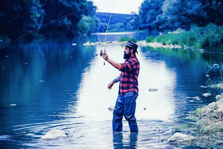 Trout. American angler fishing. Still water trout fishing. Fishing in river. Man with fishing rods on river berth. Fly angler man on the river