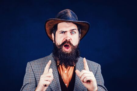 Funny brutal bearded hipster on isolated background. Close up photo of handsome funny man with beard in suit. Hand with fingers set into gun gesture.