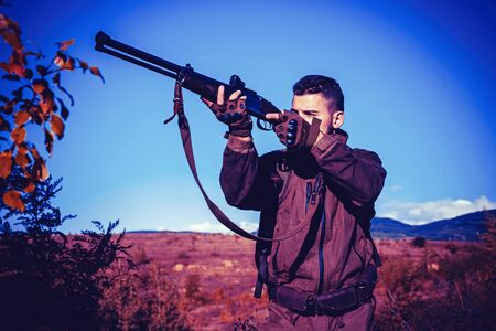 Hunter with shotgun gun on hunt. Calibers of hunting rifles. Hunter with Powerful Rifle with Scope Spotting Animals. Poacher in the Forest