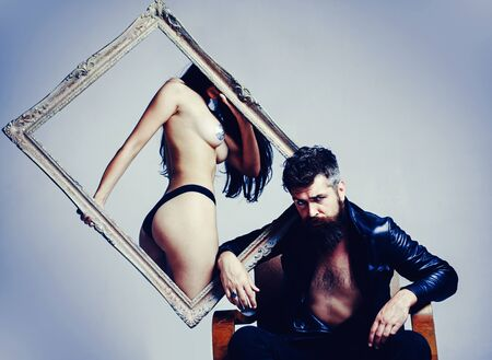 Bearded Man holds a frame and looks seriously. Temptation woman and man. Sexy Lingerie. Model is presenting the lingerie. Sexy couple play in love games. Attractive man and woman.