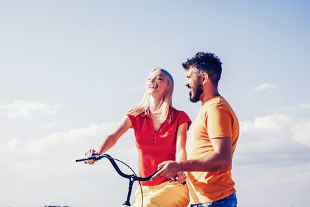 Summer woman with retro bike on blue sky background. Happy loving couple. Greatest Love Stories. Couple in summer dress rides a bike. Couple with vintage bike.