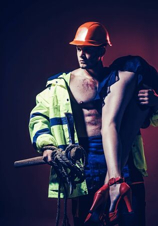 Dominating in the role play. Firefighters body muscle man holding saved woman. Risky occupations concept. Firefighter - Hot and sexy.