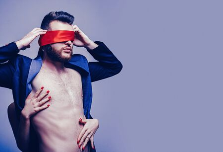 Tease and seduce. Passionate lovers. Sex domination. Sex submission. Awakening his desire. Female tease guy. Macho well groomed hipster nude torso tied eyes red ribbon. Sexual relations. Sex game 스톡 콘텐츠