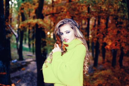 Pretty woman walking in the Park and enjoying the beautiful autumn nature. Beautiful happy smiling girl with long hair wearing stylish jacket posing in autumn day. Hello Autumn bay Summer.