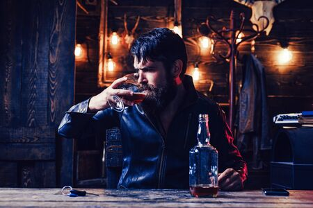 Man with beard holds glass brandy. Degustation, tasting. Handsome bearded man. Do not drink and drive.