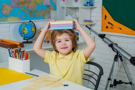 Beginning of lessons. Cute child boy in classroom near blackboard desk. Chalkboard copy space. Happy cute clever boy with book.