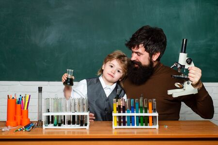 Teacher and kid. Teacher helping his teen students with chemistry or biology on education class. Teacher helping pupils studying at desks in classroom. Experiment Stock Photo
