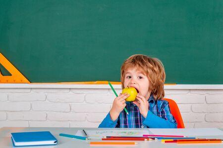 Funny child from elementary school. Child near chalkboard in school classroom. Happy school kids at lesson.