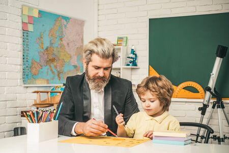 Homework help. Father helping his son to make homework. Elementary school. Pupil learning letters and numbers. Stock Photo