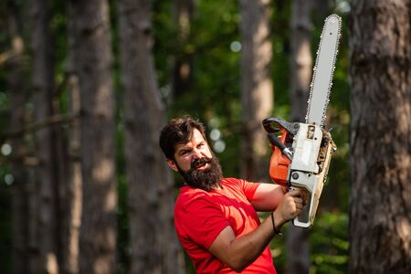 Man doing mans job. Agriculture and forestry theme. Handsome young man with axe near forest. The Lumberjack working in a forest. Firewood as a renewable energy source.