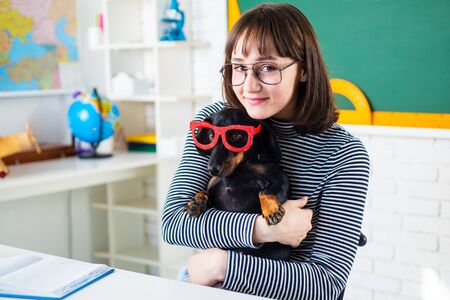 Funny teenager girl and puppi. Student with puppi. Happy smiling Student go back to school. Funny education. Funny puppy in glasses.