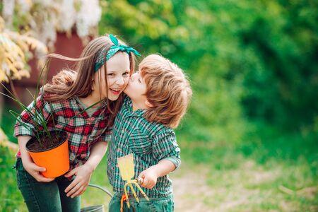Beautiful baby girl tenderly kiss boy in his cheek. Festive Art Greeting Card. Sweet childhood. Two Little farmers in village.