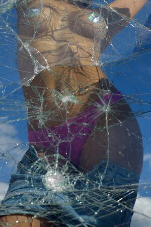 Sexy woman posing behind broken window. Sexy woman covered with shiny covers. Broken glass texture, Young hot slim woman posing at camera demonstrating body. Stock Photo