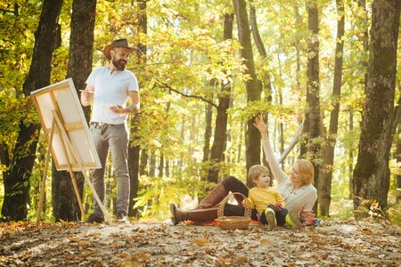 Portrait of young bearded smiling middle age white man artist drawing in open plein air outside with watercolor on paper at easel. Lifestyle activity hobby and happy family concept. Foto de archivo - 140895791