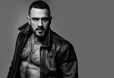 In his brutal style. Brutal hispanic man. Bearded latino man with brutal tattoo on muscular chest. Brutal and athletic, copy space Reklamní fotografie