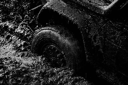 Jeep outdoors adventures. Expedition offroader. Mudding is off-roading through an area of wet mud or clay. Bottom view to big offroad car wheel on country road and mountains backdrop.