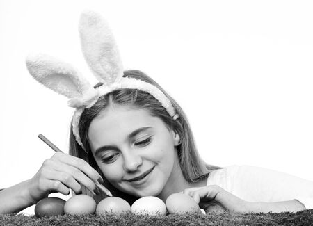 Traditional easter holidays decorations. Happy easter holidays concept. Cute smiling little girl wearing bunny ears and decorating colorful easter eggs. Reklamní fotografie