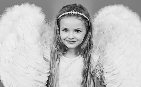 Wonderful blonde little girl in the image of an angel with white wings. Angel kid with blonde curly hair. Angel. Beautiful child angel posing and looking at camera.