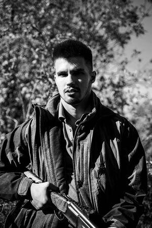 Hunter with shotgun gun on hunt. Close up Portrait of hamdsome Hunter. Man holding shotgun. Small game.
