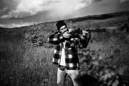 Autumn hunting season. Hunter with shotgun gun on hunt. Hunter with Powerful Rifle with Scope Spotting Animals.