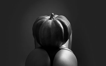 Halloween party. Sexy woman with big ass. Halloween witch with a carved pumpkin on butt. Halloween party art design. Night club and costume concept. Halloween festival decorations.