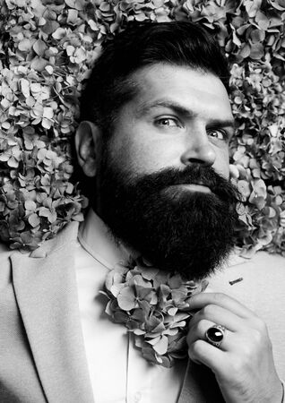 Vogue flower bow-tie. Man in blue suit. Bearded man and flower beard. Spring necktie. Elegant business man. Classical costume.