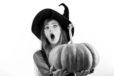 Funny face and Surprised woman. Woman posing with Pumpkin. Beautiful young surprised woman in witches hat and costume holding pumpkin. Zdjęcie Seryjne