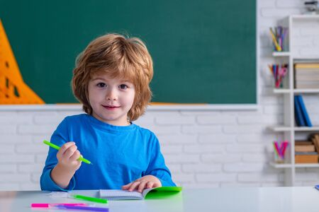 Primary school pupil. Children learning. Cute child boy in classroom near blackboard desk. Chalkboard copy space.