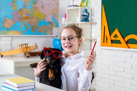 Funny puppi and pupil. Child girl with puppi. Happy smiling kid go back to school. Funny education. Funny puppy in glasses.