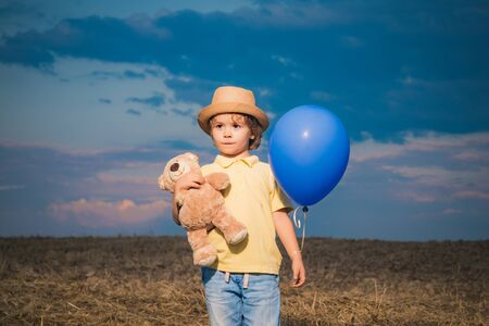 Little boy in a field with toy teddy and balloon on sunset background. Happy little boy outdoors in the garden. Happy child outdoors on summer field. Zdjęcie Seryjne