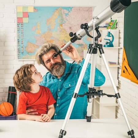 Father teaching son. Pupil watching stars with a teacher. Astronomy telescope.