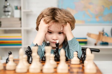 Boy think or plan about chess game, vintage style for education concept. Chess school. Boy kid playing chess at home. Stock Photo