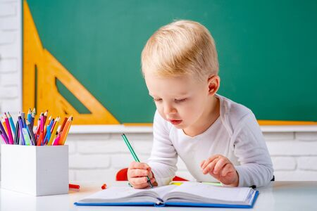 Home schooling. Child home studying and home education. Pupil learning letters and numbers. Chalkboard copy space. Banque d'images - 140645495
