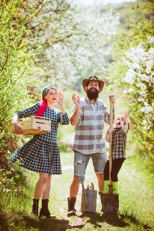 Happy family in garden. Happy family in vegetable garden. Family walking in agricultural field. Happy family Farmers working with spud on spring field. Stock Photo