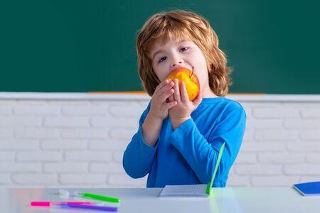 Elementary school. Funny kids from primary school eating apple. Schoolkid or preschooler learn. Cute Preschool in Classroom. Banque d'images - 140814696