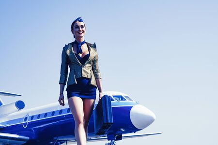 Stewardess. Journey and jet trip. Woman and commercial plane. Portrait of charming stewardess wearing in blue uniform. Stewardess and travel time. Business people and commercial jetliner. Zdjęcie Seryjne