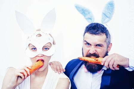 Funny easter egg couple close up. Easter egg celebrate for funny couple. Sexy bunny rabbit. Easter bunny couple eat carrot.